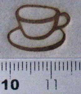 紙にコーヒーカップの焼印を押す